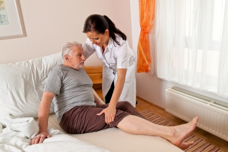 nurse helping elderly man out of bed at home