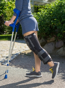 Woman with broken kneecap, with her leg in a brace, using crutches