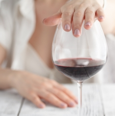 woman's hand over glass of wine refusing more