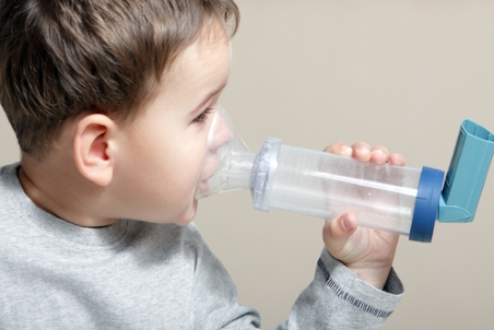 little boy using inhaler for asthma