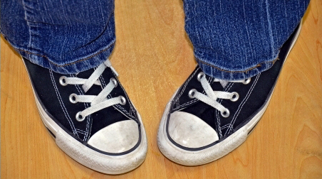 A child in sneakers with their feet pointing inwards. This is called pigeon toes or intoeing