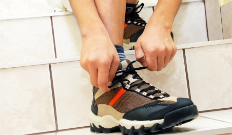 Teenager doing up laces on sports shoes, which are best if they have Sever's disease