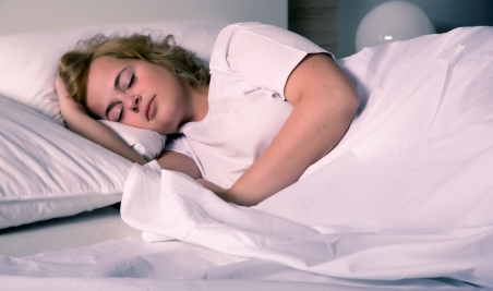 Overweight young woman asleep in bed