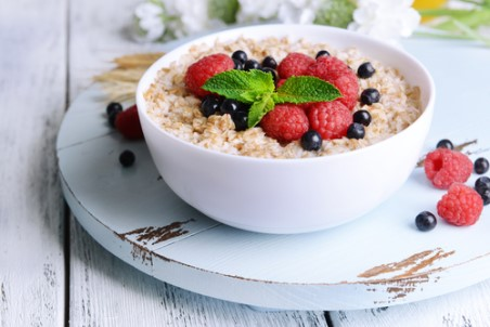A bowl of oatmeal topped with blueberries and raspberries