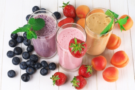 three fruit smoothies with blueberries, strawberries, and apricots