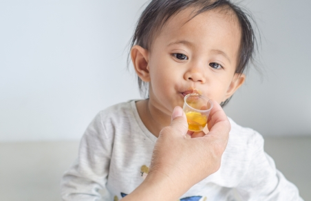 toddler taking medicine from a measuring cup