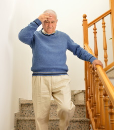 Man with vertigo holds handrail on the stairs