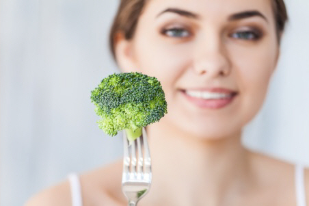 Woman eating broccoli.jpg